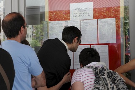 Los padres consultan las listas de admitidos en Infantil.. A. N.